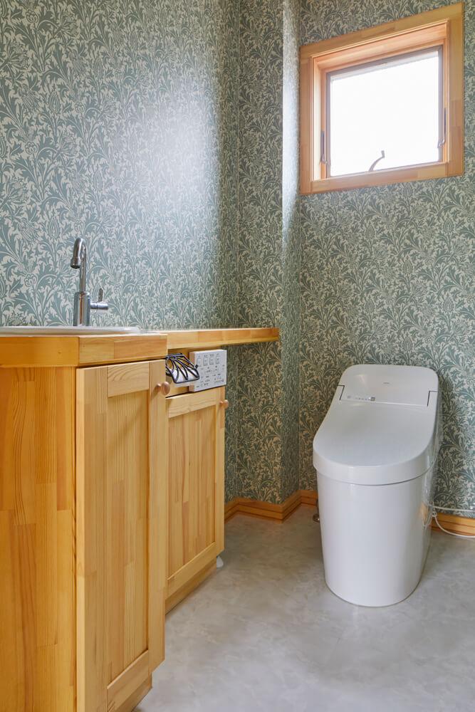 造作の手洗いカウンターを設けた1階トイレには、華やかな印象の壁紙を貼った