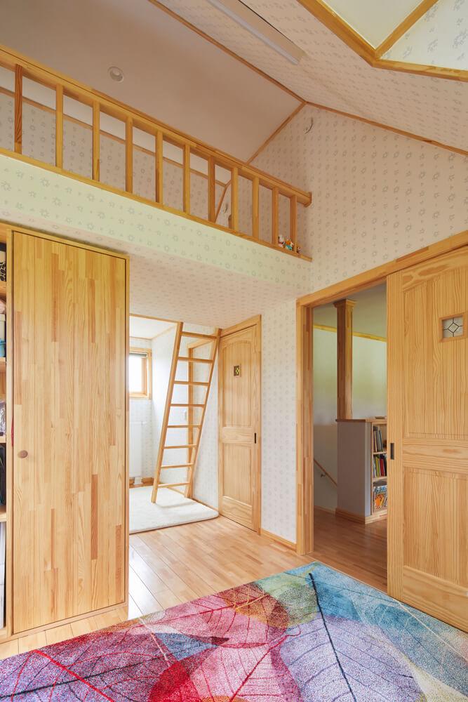 屋根なり天井を生かし、ロフトを設けた2階の子ども部屋は、造作の収納家具で間仕切りができる。ドアには、娘さんが選んだステンドグラスをはめ込んだ