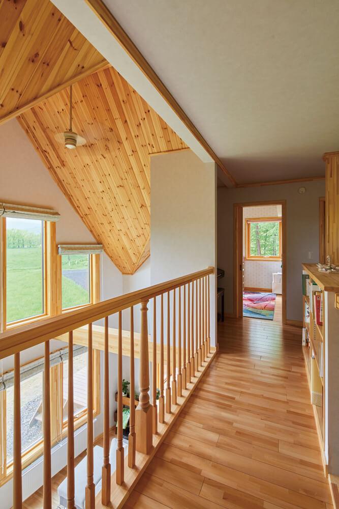 吹き抜けと階段に挟まれたブリッジのような2階廊下。階段の腰板には、本棚を造作。吹き抜けの手すりも手仕事を生かしたオリジナル
