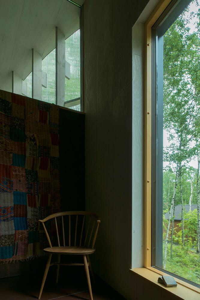 階段の踊り場にさりげなく置かれた椅子や壁に掛けられたテキスタイルが、室内空間や周囲の環境によく似合う