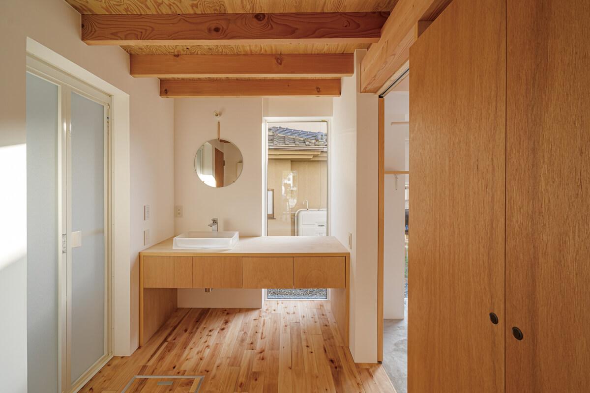 キッチンの並びに配した明るい洗面脱衣室。洗面台はこの家に合わせたオーダーメイド