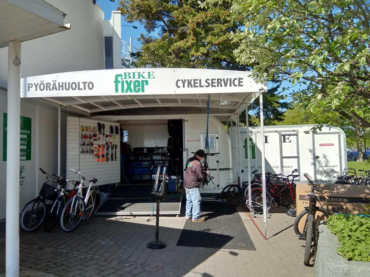 人気カフェのメインエントランスの隣にある、自転車修理の専門店