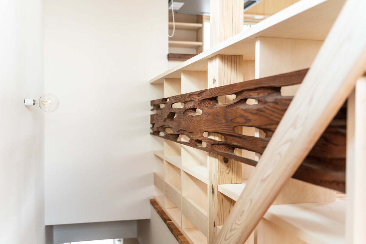 階段に面して造りつけた本棚の背面には、旧宅の和室の欄間板をはめ込んだ