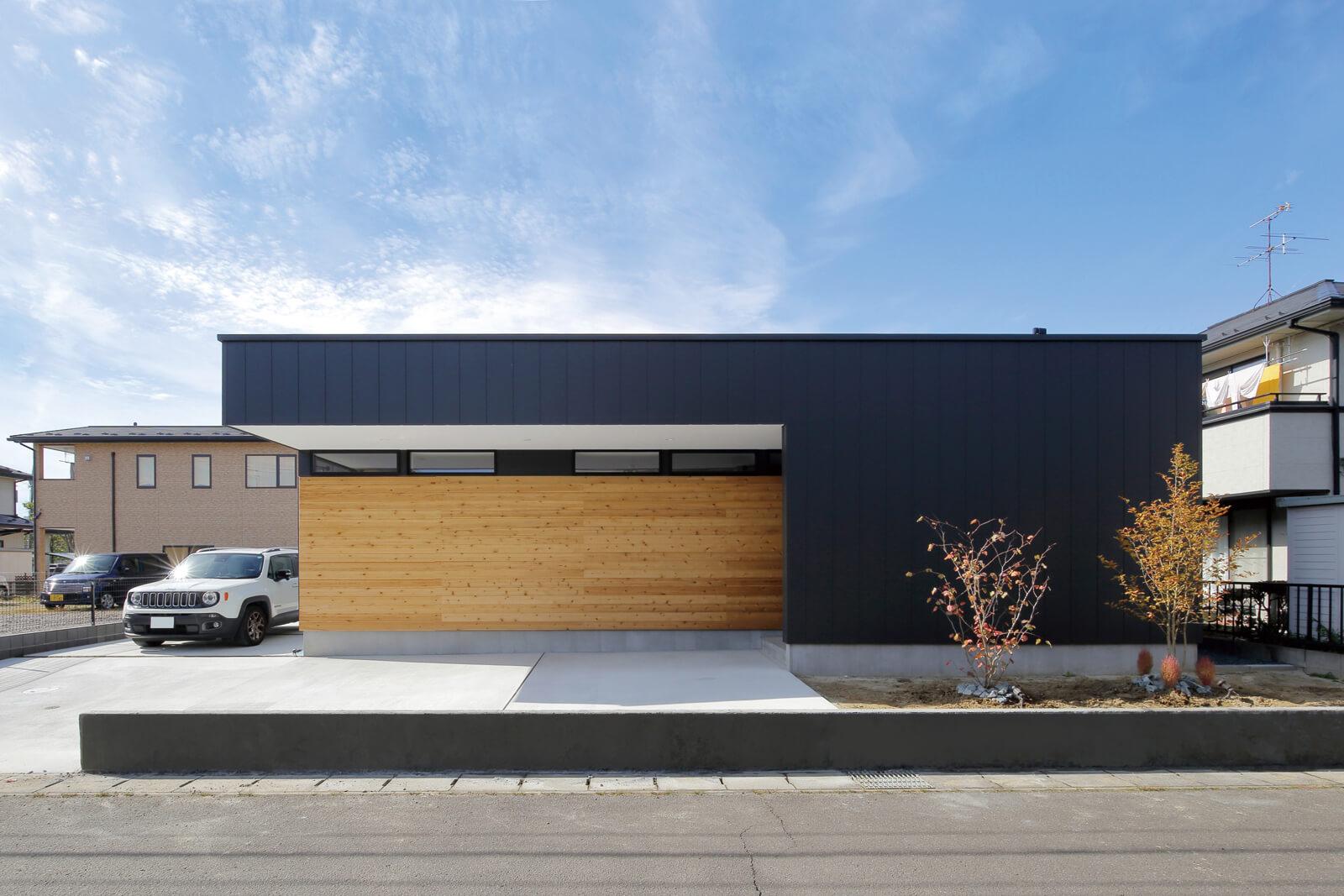 黒い外壁に木板張りと大きな庇が特徴的な外観