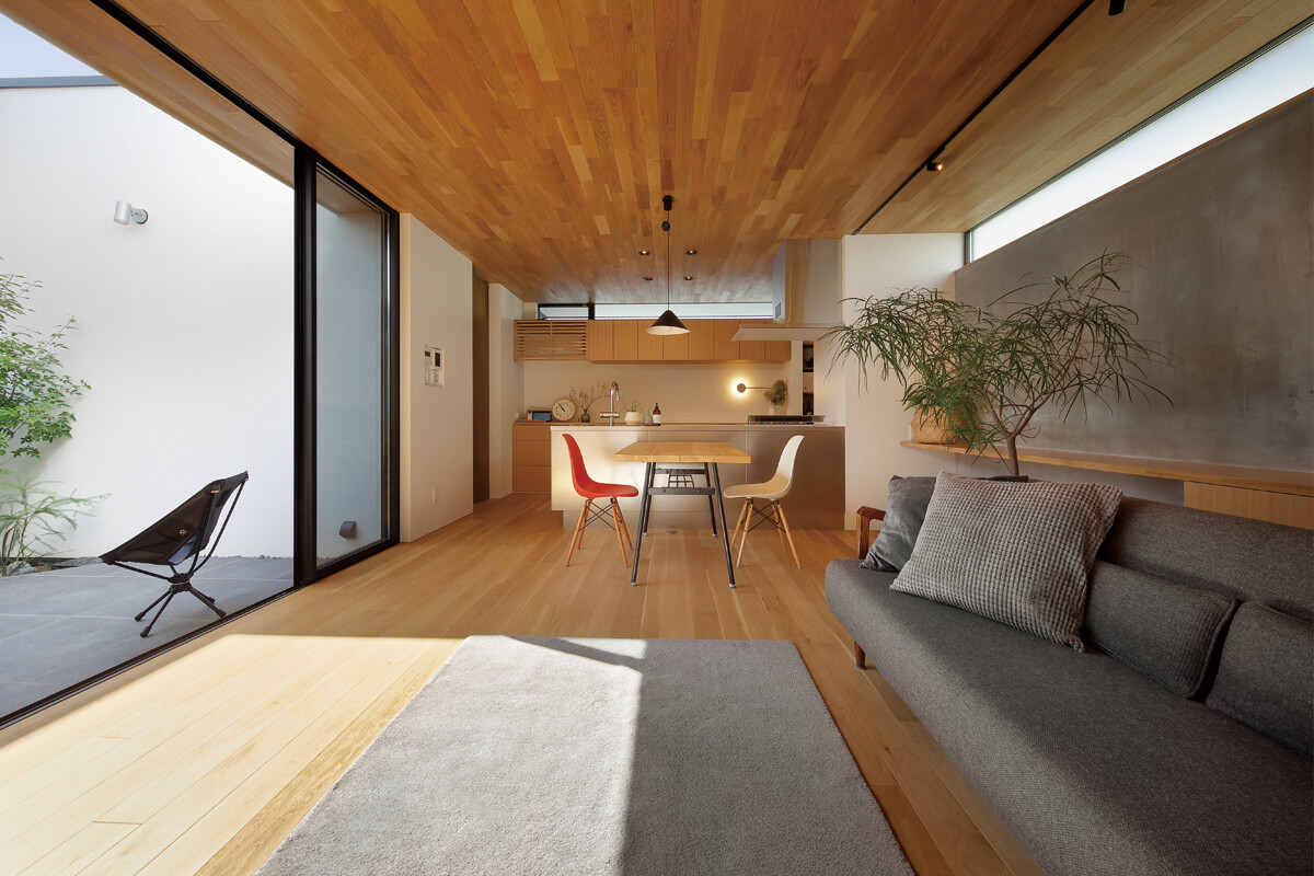 キッチンは対面に。背面収納の上にスリット状のハイサイドライトを設けた