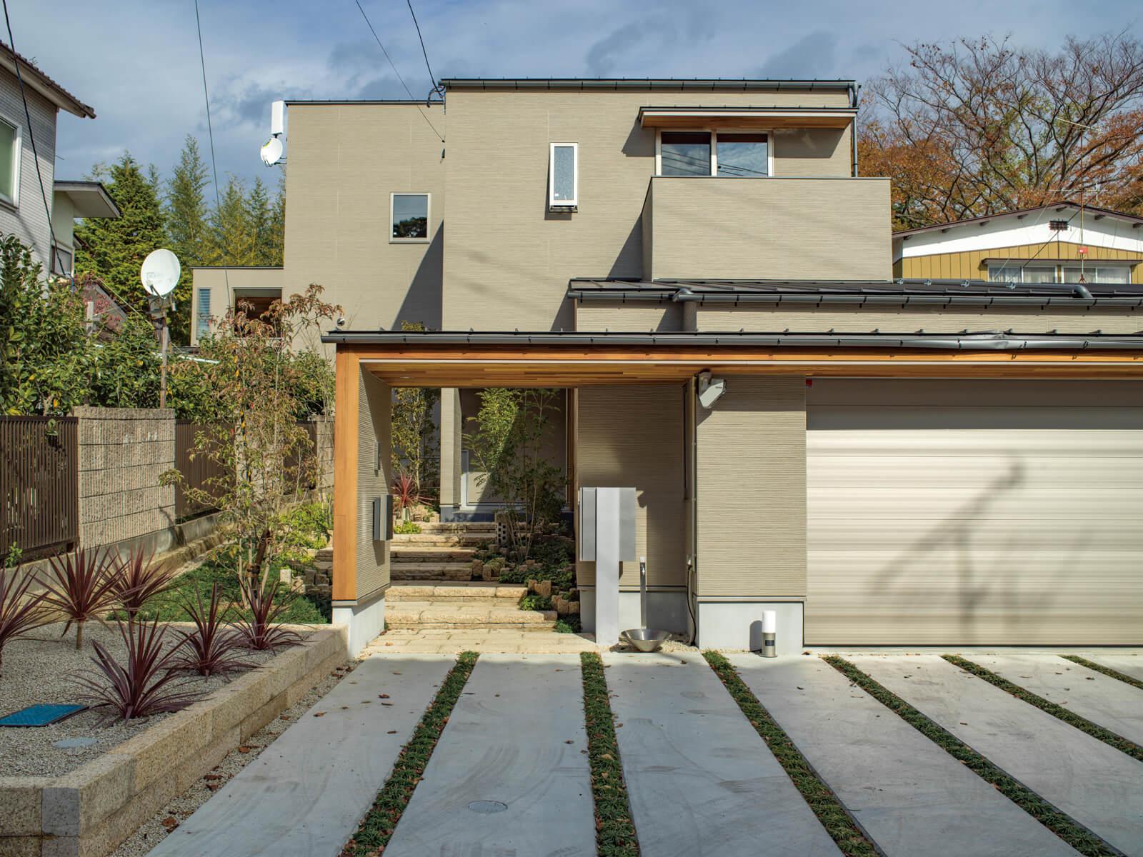 低く構えた家の門は、ガレージに組み込んで建物と一体感を持たせた