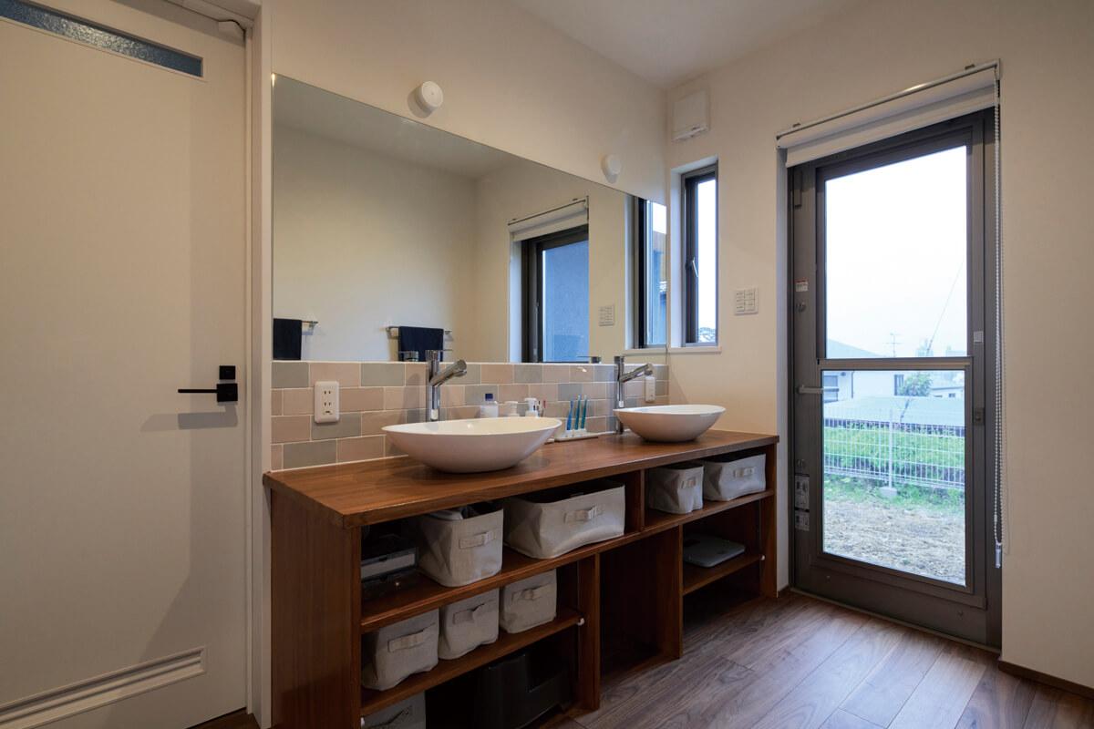 洗面台はツインボウルで、並んで身支度ができる。左の扉は脱衣室、バスルームへと続く