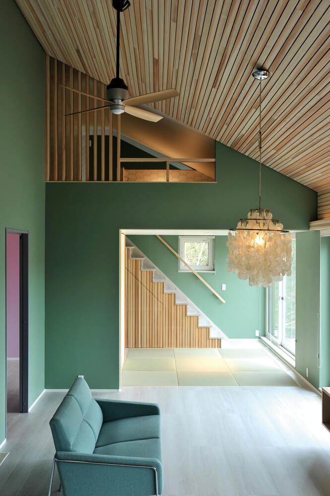 リビングは、高さ4m以上のスギ柾目板仕上げの勾配天井。暖房は床下エアコンで、冬季でも24℃以上の室温をキープできる