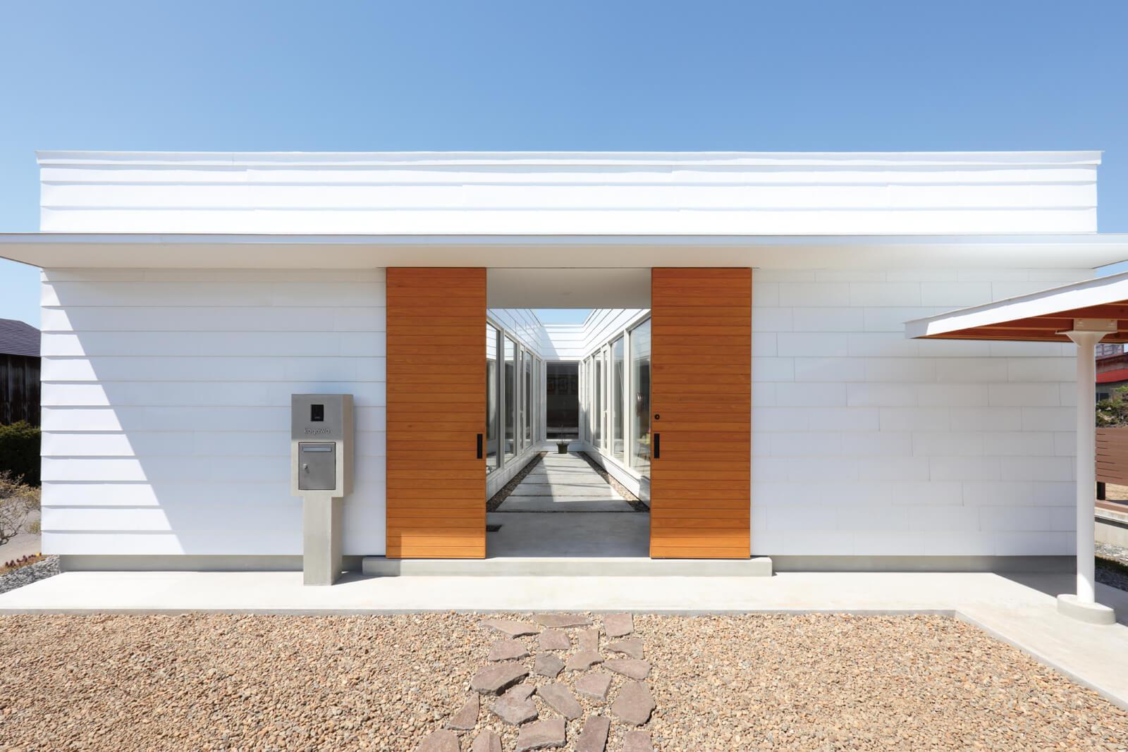 住宅の東側外観。大きな門の奥にテラスが続く。公的な性格の庭に対し、門が距離感を調節する役割を果たす