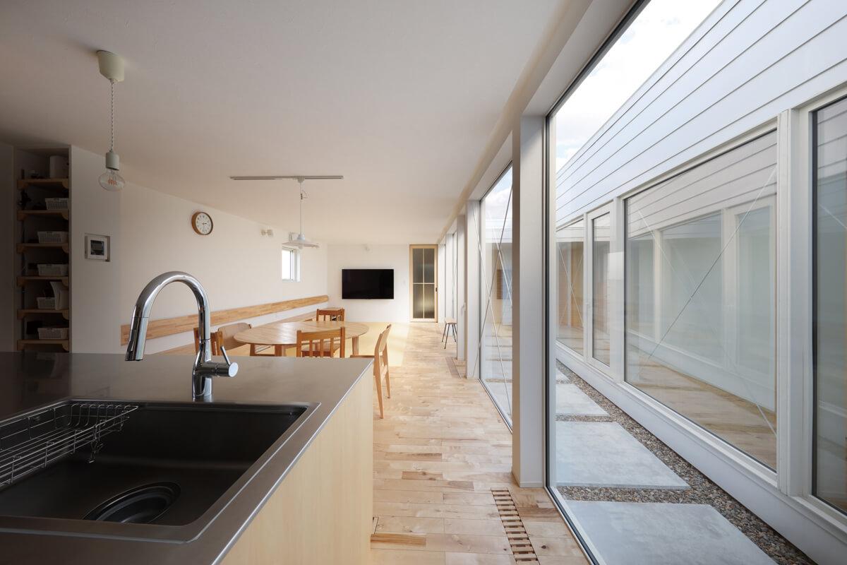 キッチンからリビング方向を見る。テラスを挟んで右側は寝室棟で、つかず離れずの距離感を持たせている