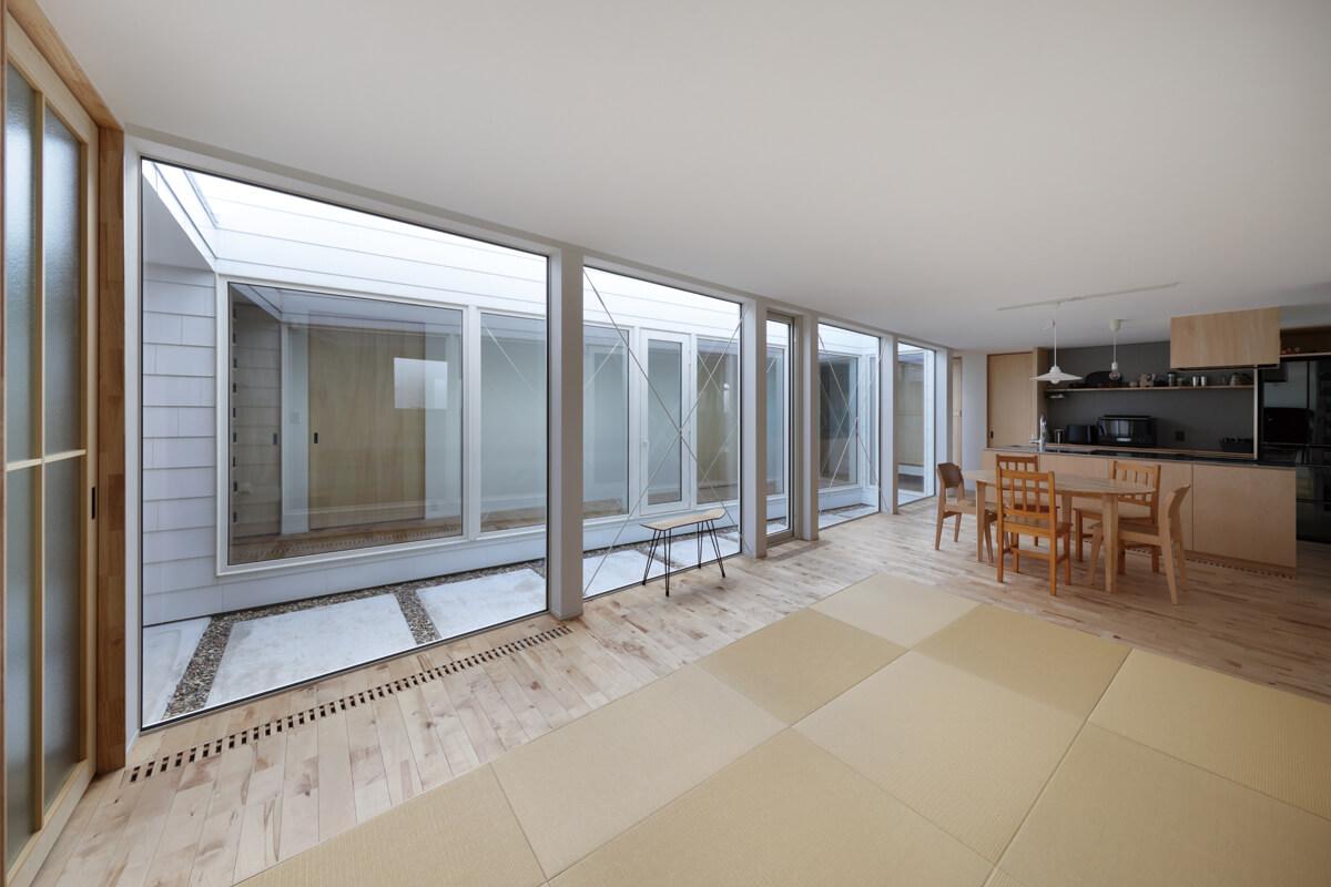 リビングから寝室棟方向を見る。天井は2.2mと低く抑えつつ、大きな開口で水平方向の広がりが感じられる