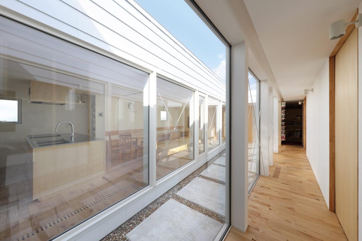 縁側のような雰囲気を持つ長い廊下。天井までの開口が内と外をつなぐ