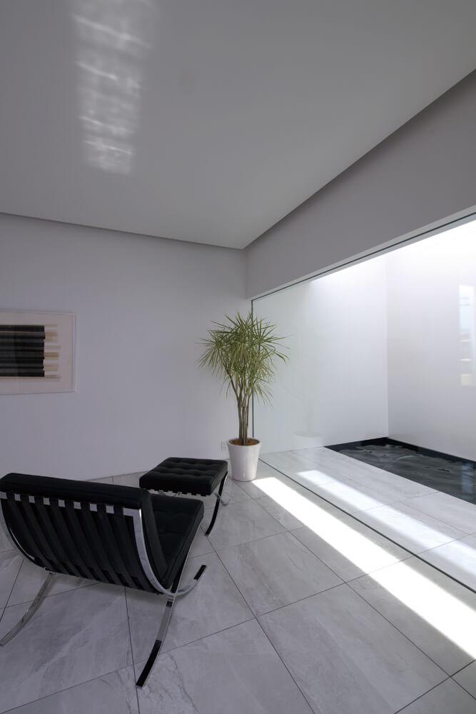 リビングからガラス越しに見える水盤のある中庭に自然光が注ぐ