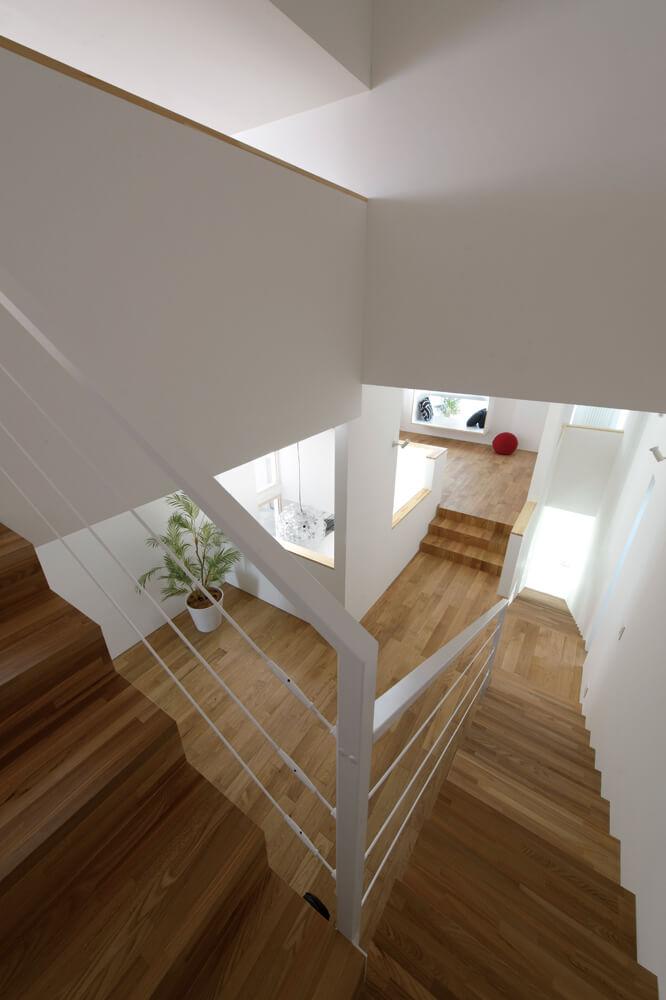 ロフトへの階段から2階フロアを見下ろす。リビング上部は階段3段分持ち上げられている