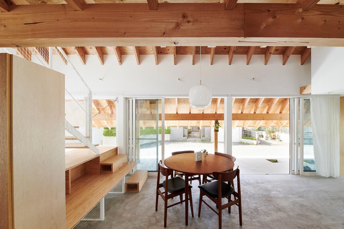 大屋根の軒先を低く落とし込んだ設計で、西陽と周辺の住宅からの視線を遮って囲いながら外へ開いた