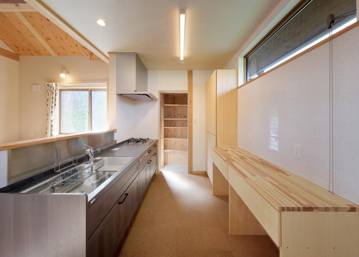 背面に広い造作の作業台のある機能的な対面式キッチン。奥にはパントリーも設けた