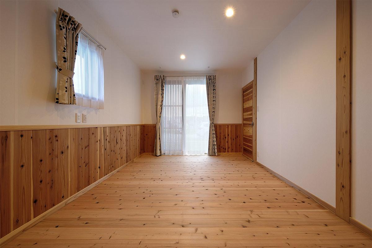 杉無垢材のフローリングと腰板を張って仕上げた1階寝室