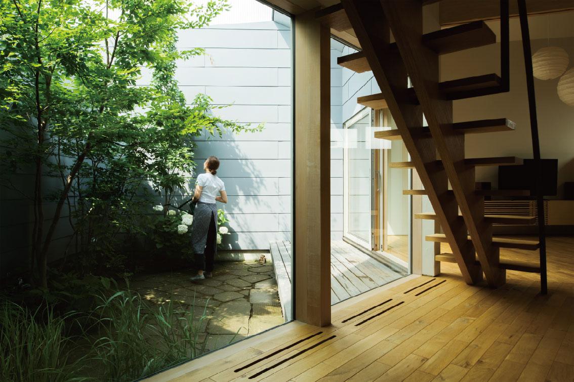 幅広のウッドデッキはどこか懐かしい縁側の雰囲気でソトとウチを繋ぐ。地面には風合いのよい札幌軟石の敷石を埋め込み、色数を絞っている