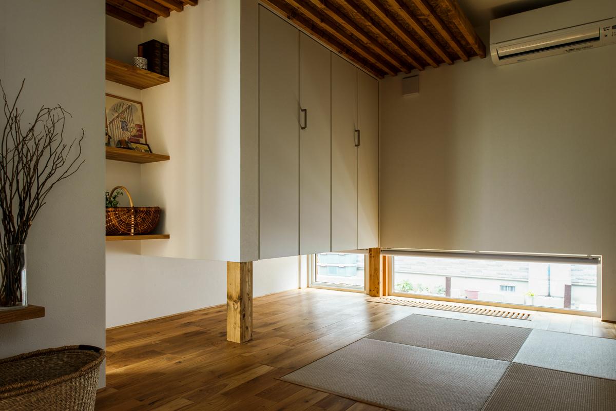 間仕切りなくリビングからそのままつながる和室。琉球畳と地窓、吊り押し入れを採用し、広がり感のある和モダン空間に仕上げた
