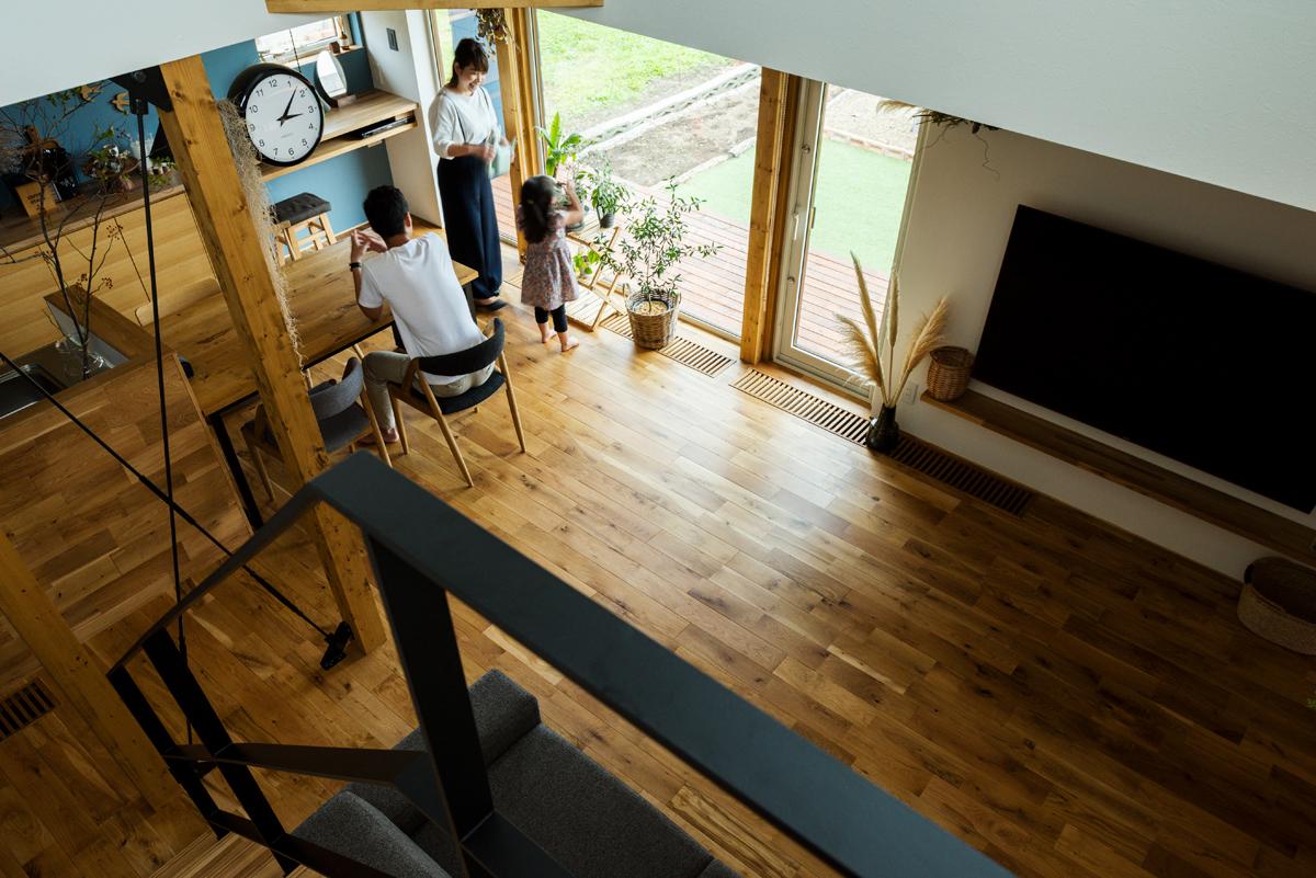 階段からダイニング・キッチンを見る。階段の吹き抜けは、1階にいる家族の気配を2階へ伝える役割も果たす
