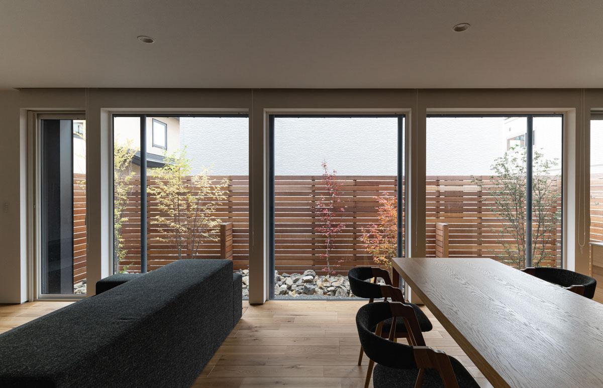 LDKに沿って設けられた壁一面の大きな窓の向こうには裏庭。テラスには長めの庇をつけ光を遮る工夫も