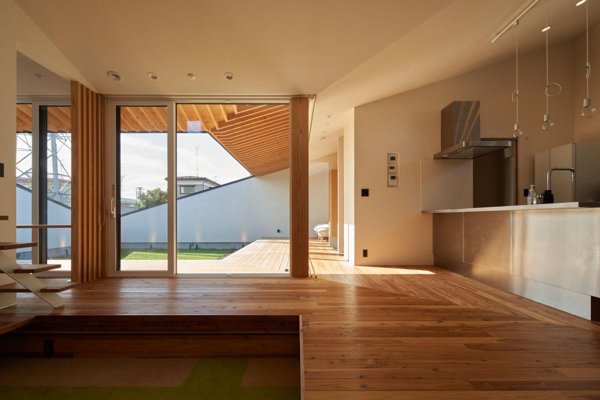 家のほぼ中央に位置した対面キッチンからは、外も室内も一望できる。リビングにはダウンフロアを採用した