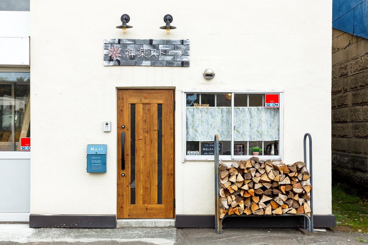 木製扉が目を引く玄関まわり。外に置かれた薪棚がお店の目印に