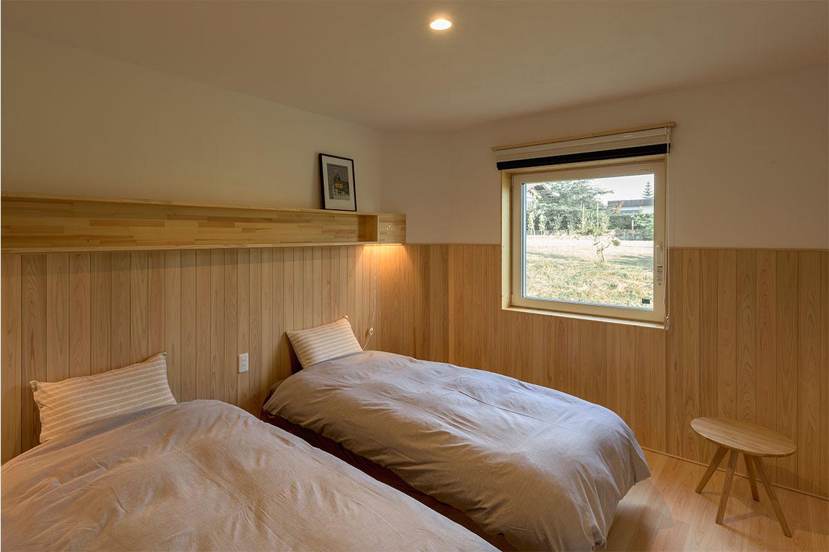 壁の半分以上を木板張りで仕上げた、木質感あふれる寝室。天井をあえて低めにして、落ち着きのあるこもり感を演出している