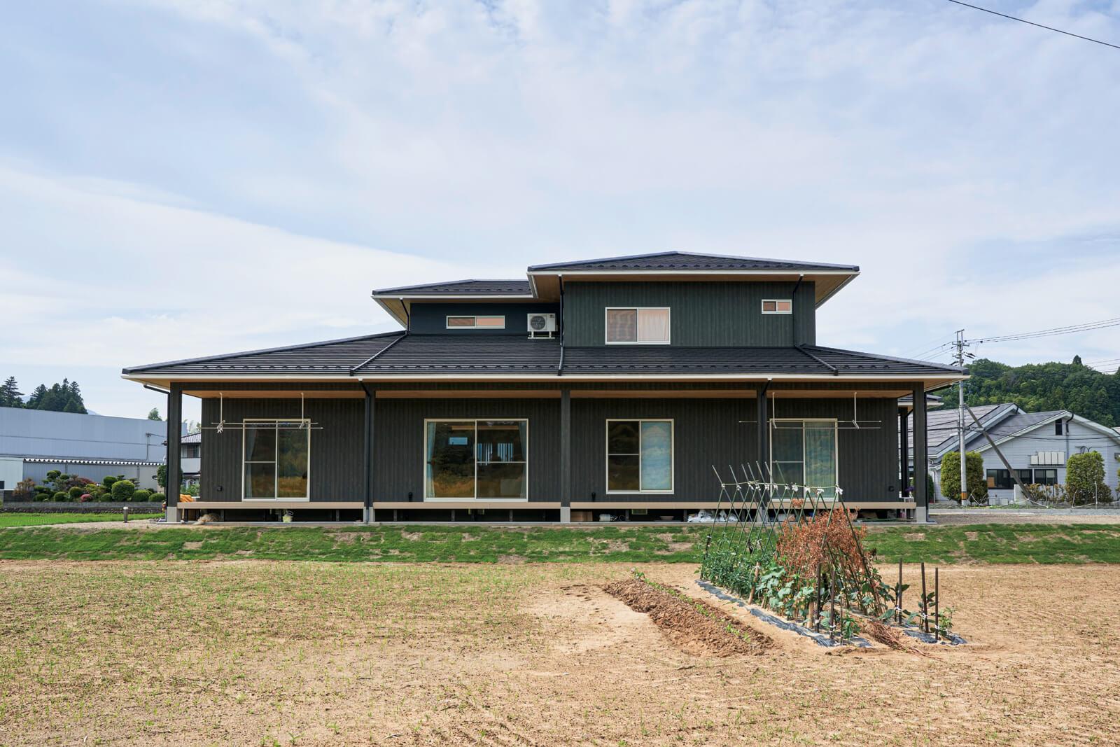 深緑色の外壁が周囲の自然に溶け込む。長期優良住宅の認定を受けた性能面でも高水準の住まい