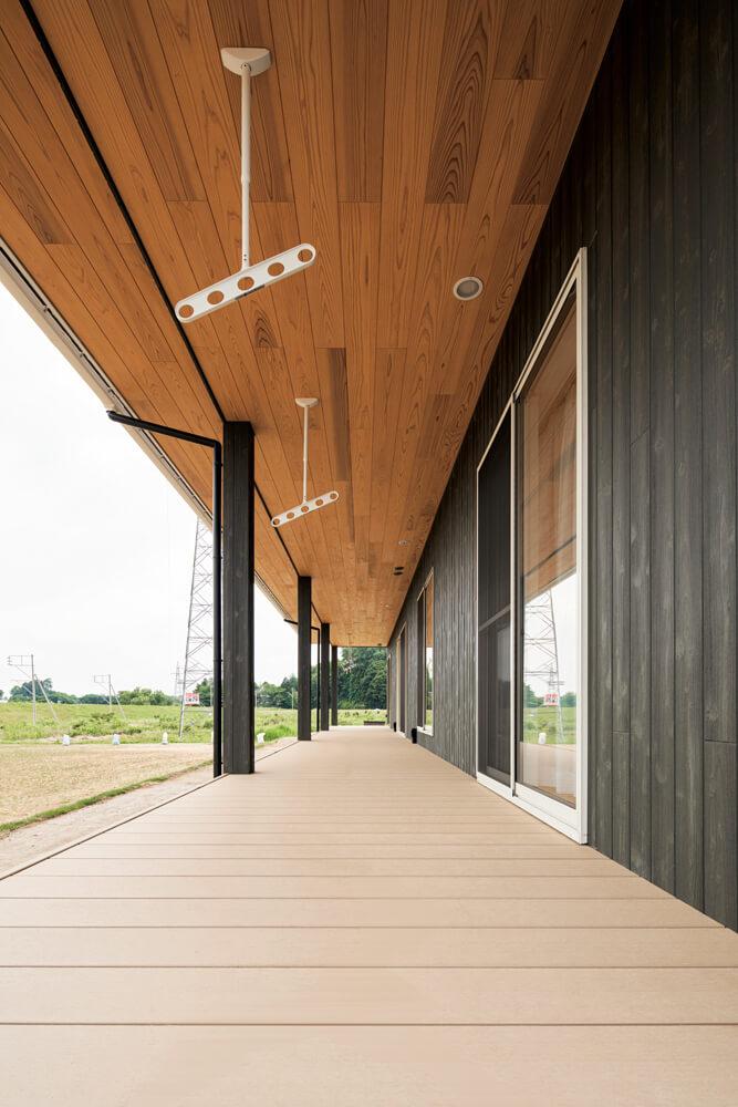 家の端から端まで延びるウッドデッキは屋根付きで使い勝手抜群。軒天には見栄えの良い無節の日光杉を使用