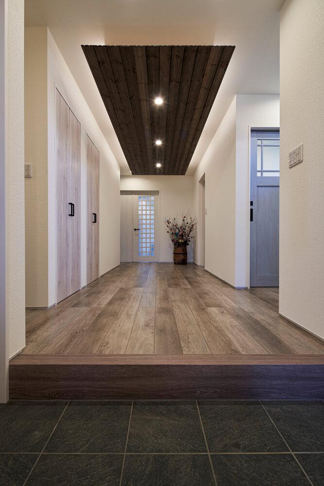 玄関からの眺め。奥の扉の先がLDK。ダークブラウンの飾り天井が上質感を添える