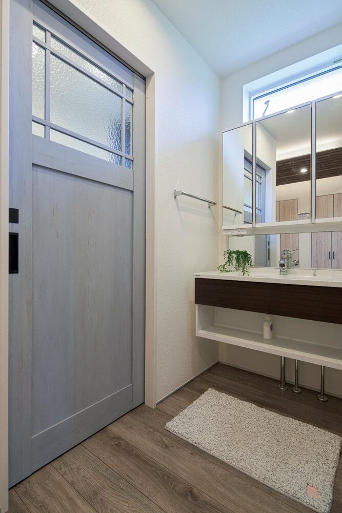 落ち着いた雰囲気の洗面コーナー。トイレに続くカフェ風の扉がヴィンテージ感を高めている