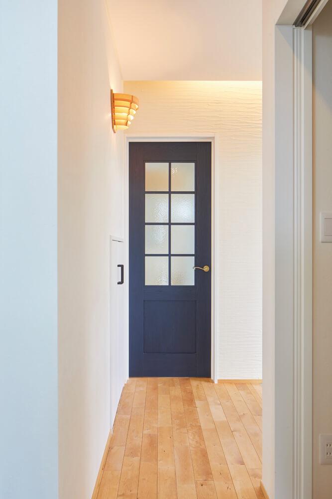 玄関ホールからリビングへ続く室内ドア。珪藻土の塗り壁に濃いネイビーが映える