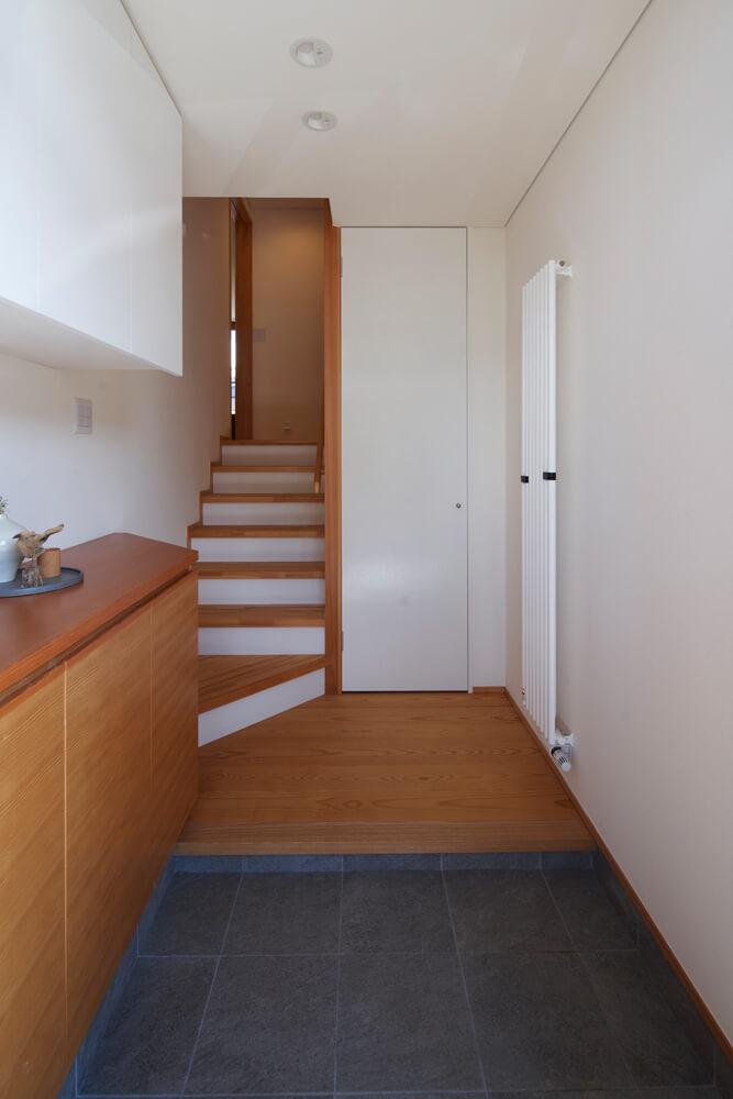 造作のシューズボックスが配された収納力豊富な玄関。階段を上がった先にLDKが広がる