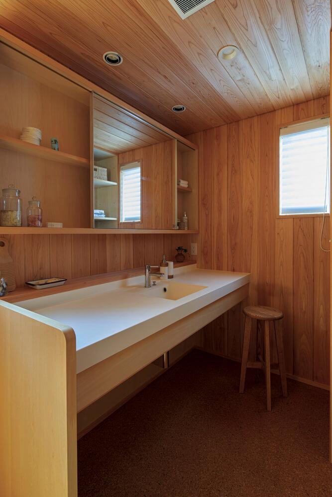 造作の洗面化粧台がおしゃれな洗面脱衣室。浴室との一体感を出すため、天井や壁にはサワラを張っている