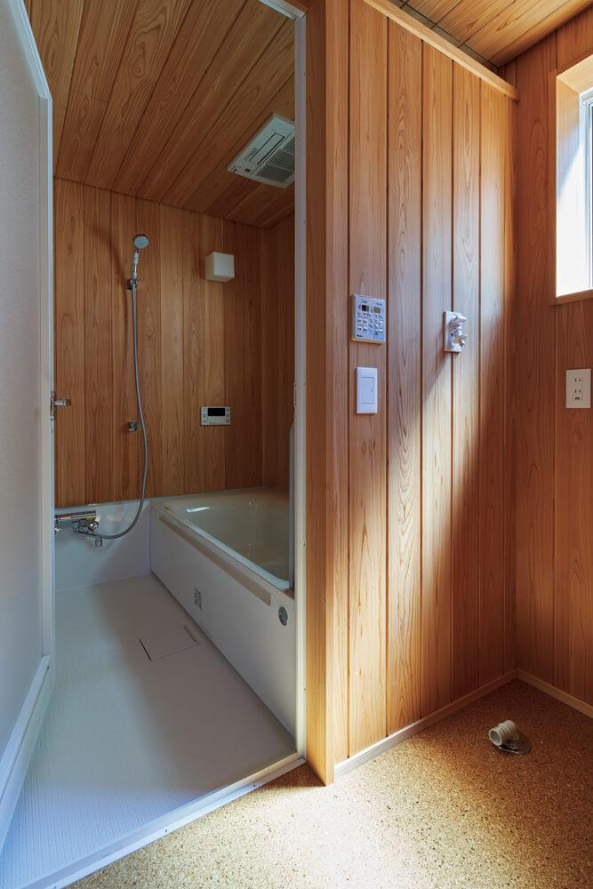 リラックスできる浴室はハーフユニットを採用。天井と壁の上部をサワラ板張りにし、上質感を演出した