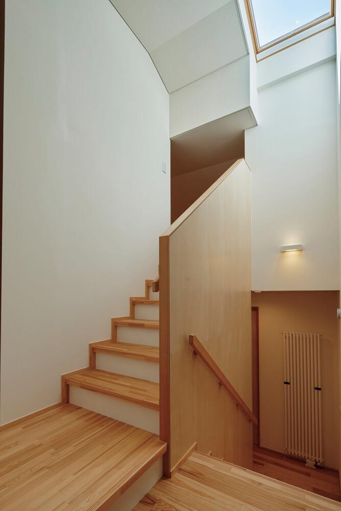 階段は幅広で上り下りしやすい仕様。東西には隣家が迫っているため、天窓や高窓などを活用して明るさを確保している
