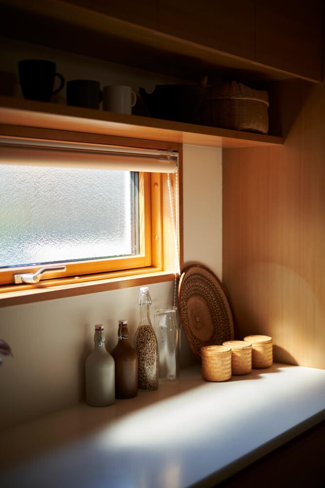 キッチン背面にも造作の収納棚をレイアウト。断熱性に優れた木製サッシの窓からやわらかな光が注ぎ込む