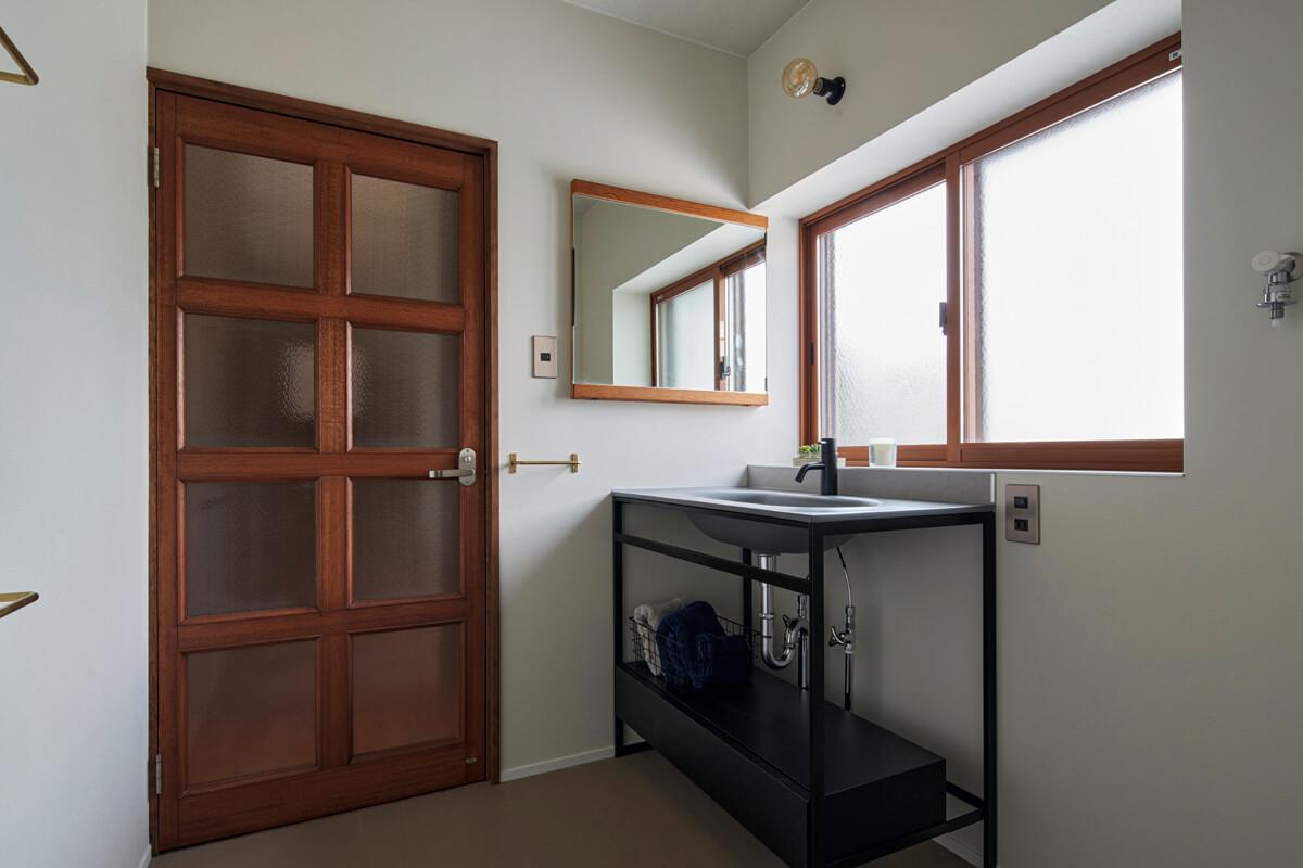 以前はキッチンの入り口に設けられていた建具を洗面脱衣室に。前の住人であるおばあさんが使っていた化粧台の鏡も再利用