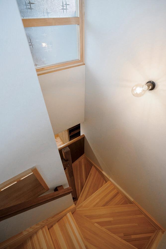 上り下りのしやすさに配慮した回り階段。暗くなりがちな北側に位置するため、かすみ模様の型ガラスを「光のスクリーン」として再利用し、明るさを確保した