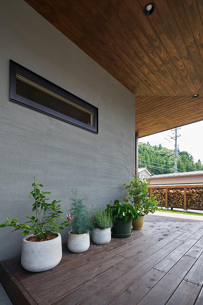 落ち着いた色合いの塗り壁と木の温もりあふれる軒天井が上質感を演出。ウッドデッキにはIさんが丹精込めて育てている植物が並ぶ