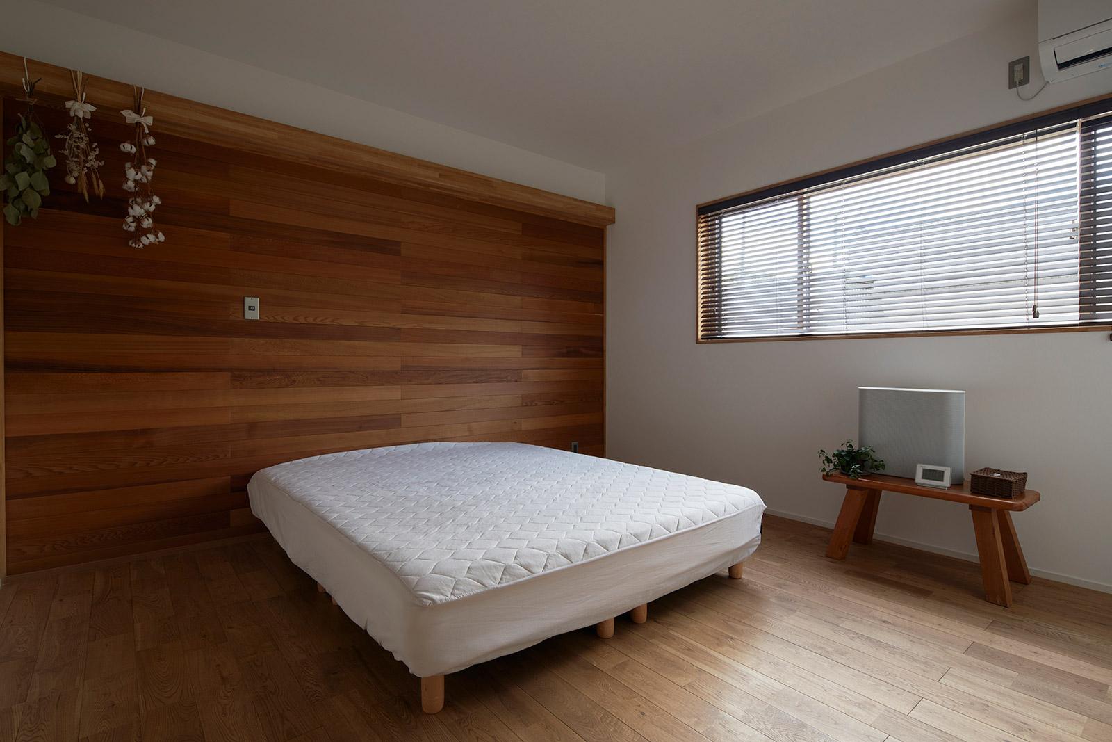 階段の上り下りが辛くなる数十年後を見据え、寝室は1階にレイアウト。壁一面のレッドシダーが温かみを醸す