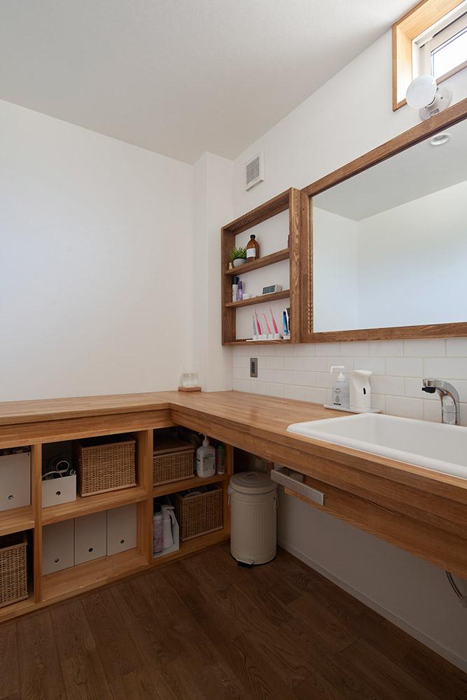 L字型に配置された造作の洗面台と収納カウンター。ミラーやキャビネットまで造作で、一体感のある空間に仕上がっている