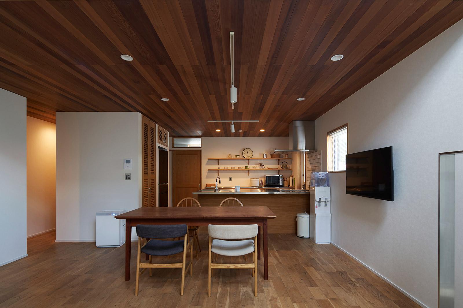 白壁にナラの無垢床、レッドシダー羽目板の天井が映えるLDK。シンプルながらも洗練された美を感じる空間