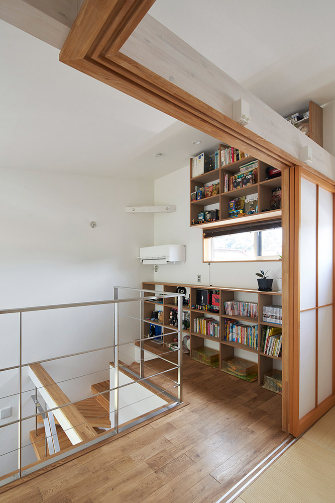 階段を上りきった位置に設置されたエアコンが吹き抜けを通して冷気を1階に届ける