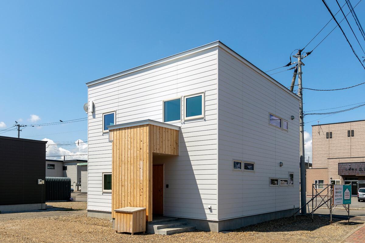 白の金属サイディングと、玄関まわりにあしらった木の組み合わせがやさしい印象の外観