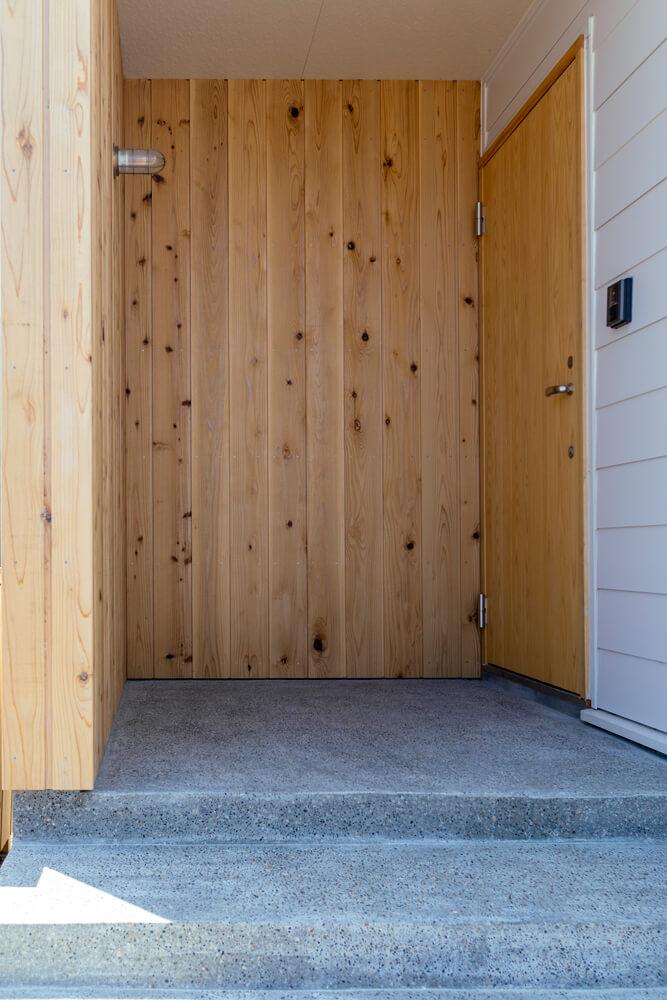 L字型に板壁で囲い、どんな天候でも安心な玄関まわり。外階段とポーチの床は、職人の技術が光る洗い出し仕上げで上質さが感じられる