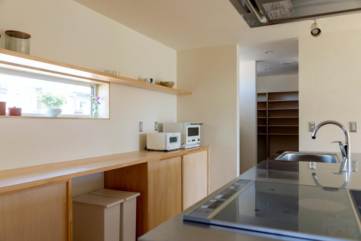 造作キッチンは、パントリーに冷蔵庫の収納場所を確保することですっきりとした空間に