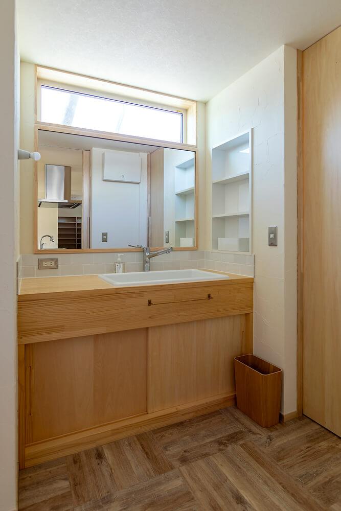 ダイニングキッチンのすぐ隣に配した水まわり。造作の洗面台は使い勝手を考え、脱衣室と分けて設計している