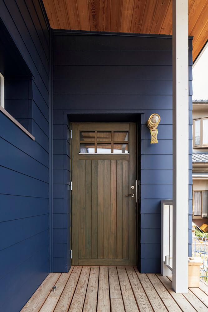 ブルーの外壁に緑がかった玄関ドア、軒裏のレッドシダー、屋久杉のウッドデッキが調和する